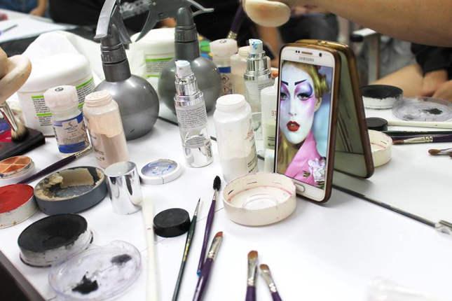 Detalle de una mesa con herramientas de maquillaje y foto del master de maquillaje
